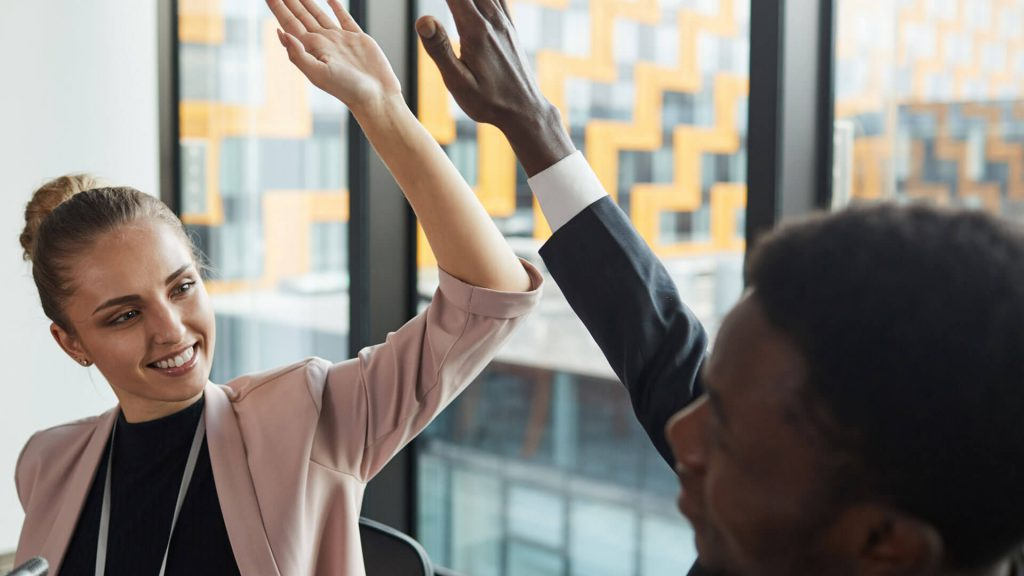 Male and female work colleagues high-fiving at desk