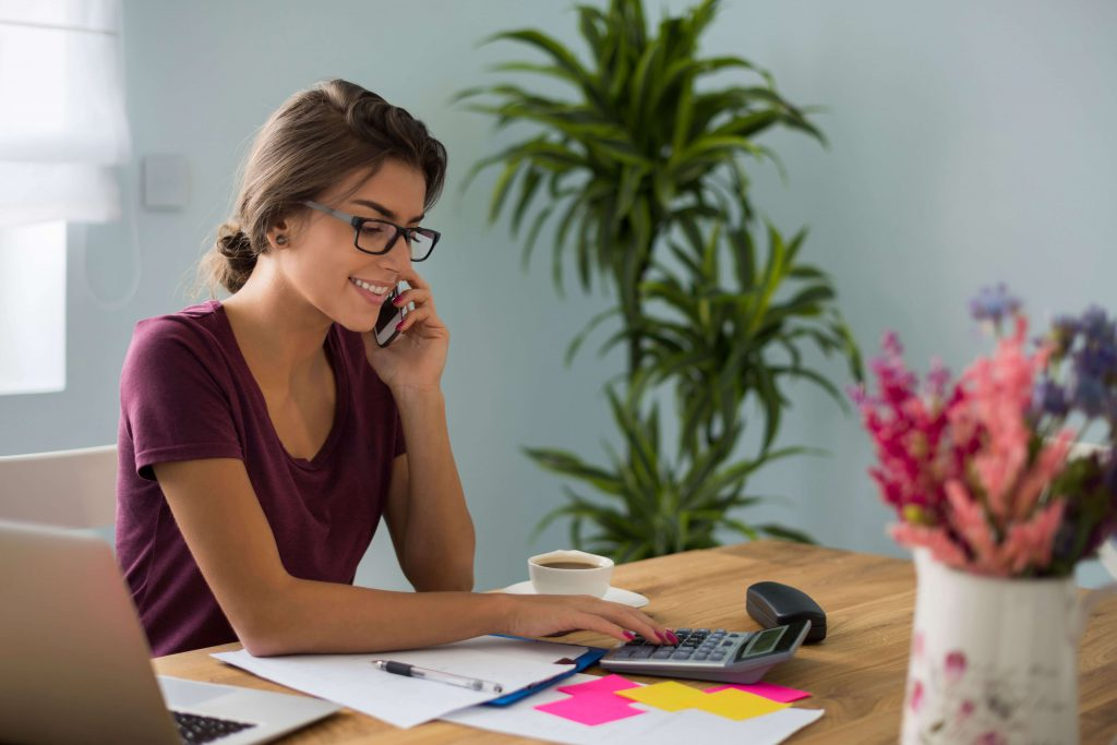 Female sat on phone at desk working on calculator
