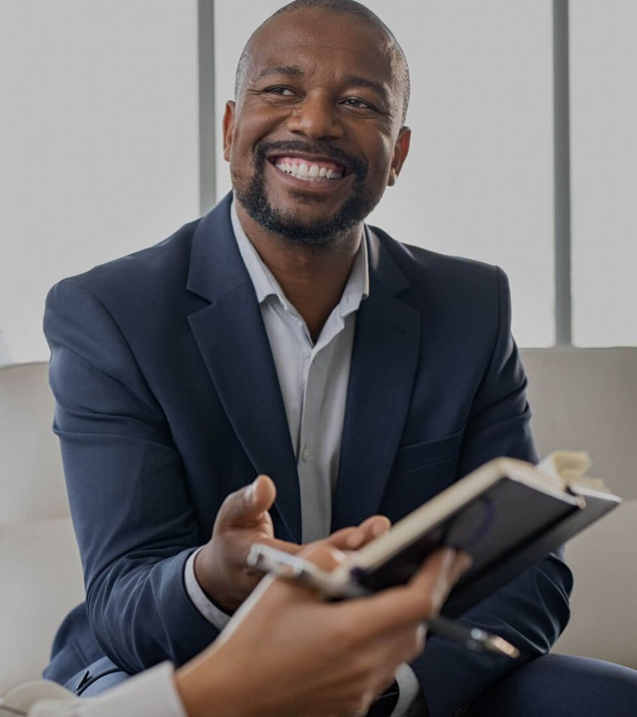 Business man with someone smiling and gesturing to book