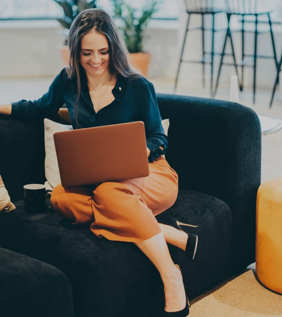 Smartly dressed female sat with laptop on her lap