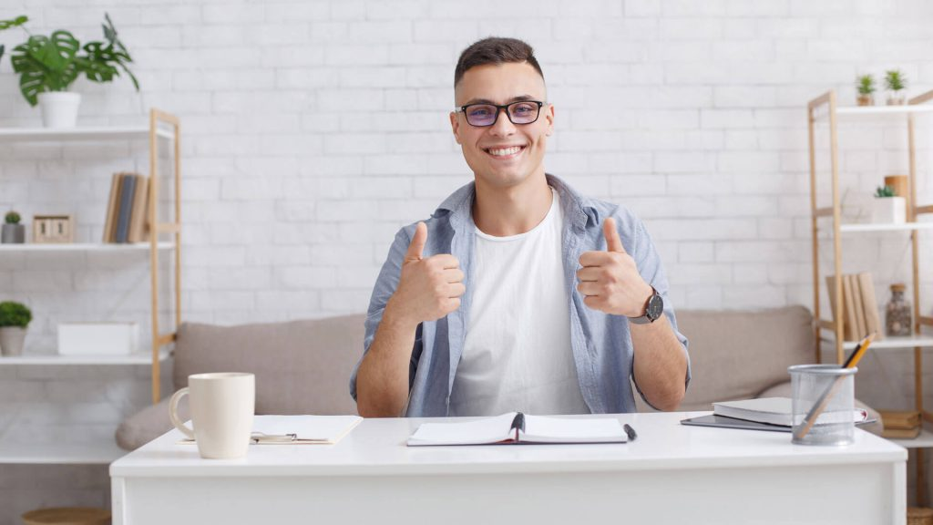 Sole business owner sat at desk with thumbs up