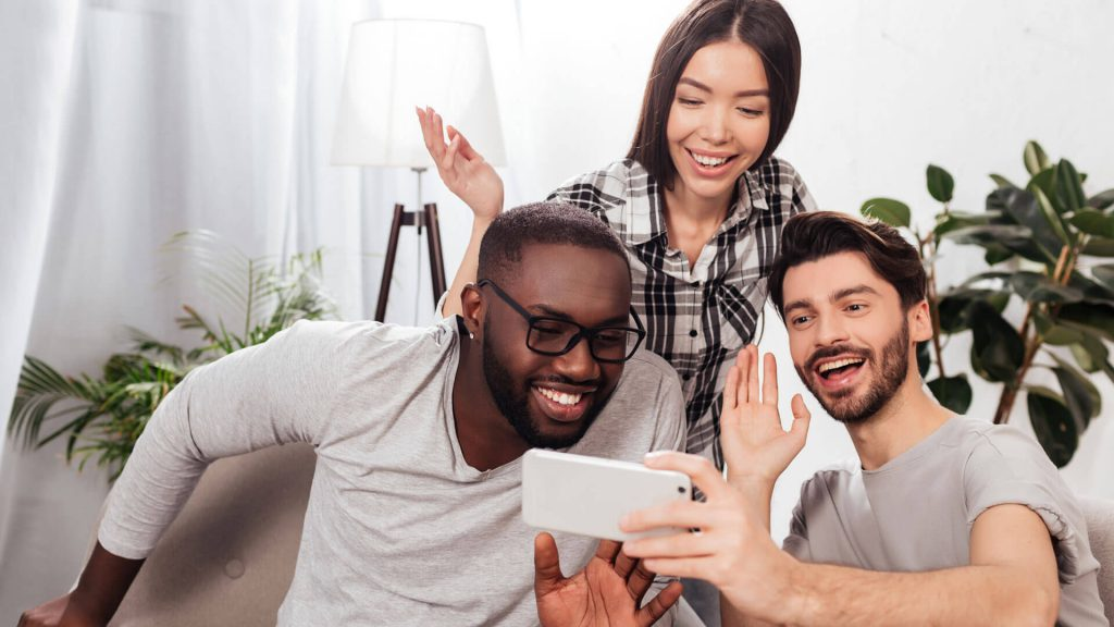 Three friends facetiming on mobile device and waving